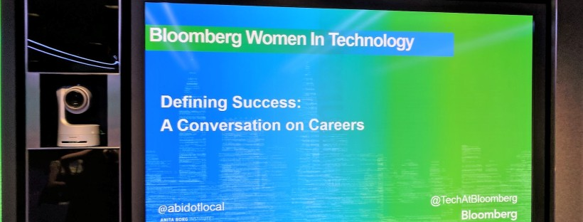 "A photo of a television screen displaying the title, ""Bloomberg Women in Technology – Defining Success: A Conversation on Careers."""